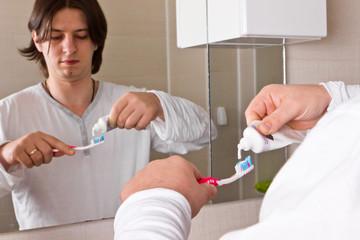 Man brushing teeth in bathroom