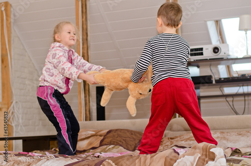 Cute brother and sister having a tug of war