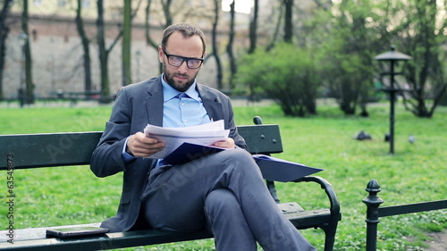 Young businessman writing notes in documents in the park