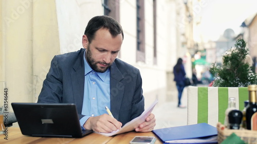 Businessman working with laptop and documents in cafe