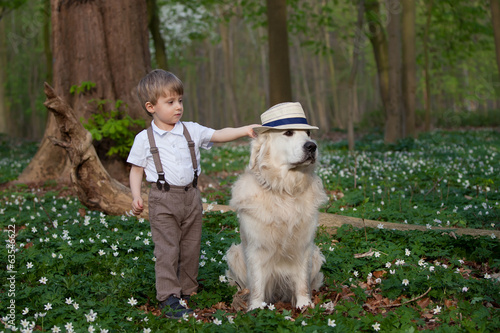 Two years old boy putting a hat on his dog.