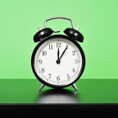 mechanical alarm clock on a bedside table