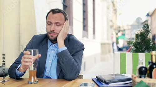 Sad, tired young businessman drinking beer in cafe
