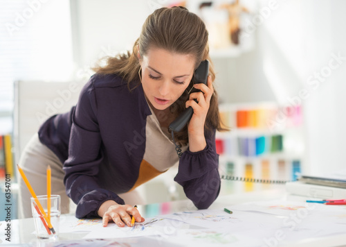 Fashion designer talking phone at work