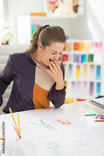 Fashion designer in office yawing