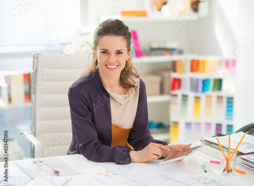 canvas print picture Happy fashion designer with tablet pc in office
