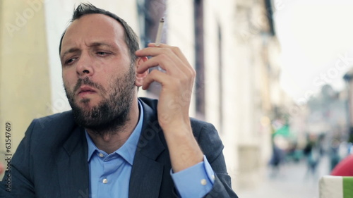 Young businessman smoking cigarette in cafe