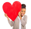 happy african woman holding red heart symbol
