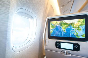 Seat monitor near window in passenger plane.