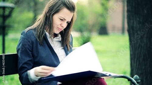 Overwhelmed, sad businesswoman with documents in the park