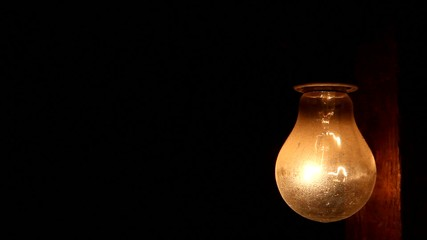 turn on and off light bulb hanging on a wooden beam