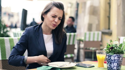 Businesswoman gets stomach ache during lunch in cafe