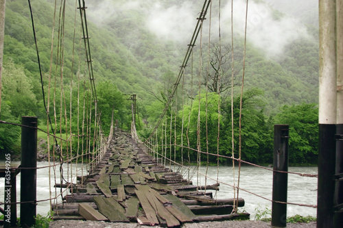 Suspension bridge over the mountain river