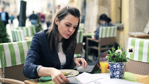 Businesswoman working with laptop and documents during lunch