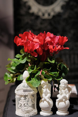 Two statuettes of angels and red flowers