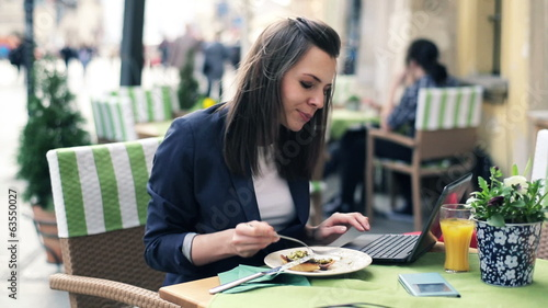 Businesswoman working on laptop during lunch in cafe