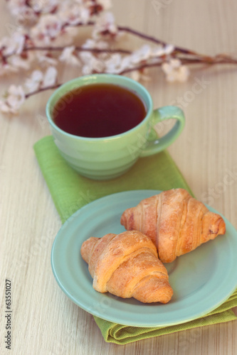 Cup of tea and croissants near blossoming branches