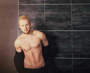 Handsome muscular male model near the wall