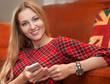 Portrait of happy woman with mobile phone sitting on floor at ho