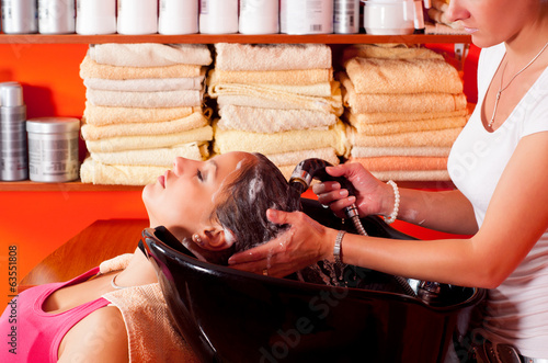 Young girl enjoying hair washing in beauty salon