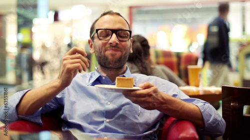 Happy young man eating delicious cake in cafe