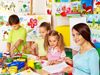 Children with teacher painting.