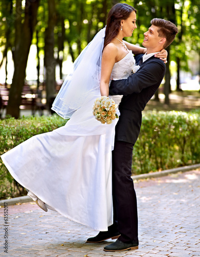 Bride and groom with flower outdoor.
