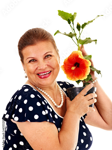 Senior woman holding flower.