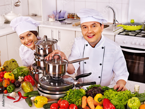 Man in chef hat and woman cooking .