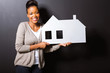 young woman holding white paper house