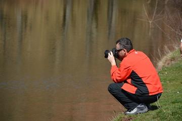 Fotografo fotografiando en un estanque en un dia de primavera