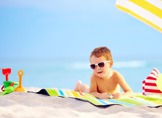 cute boy kid sunbathing on the beach