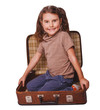 girl brunette baby sitting in a suitcase for travel isolated on