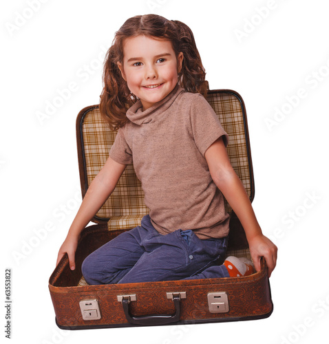 girl baby brunette sitting in a suitcase for travel isolated on