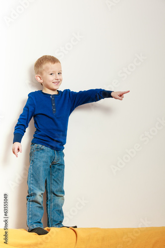 Boy child kid preschooler standing on back rest of sofa interior