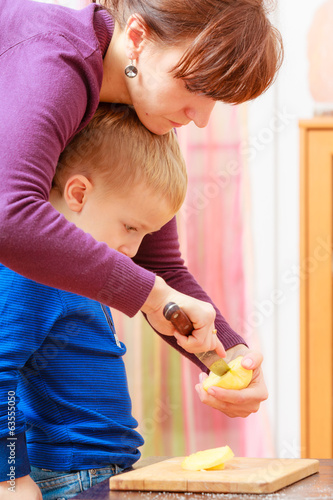 Mother teaching son how slicing apple fruit. Cooking at home.