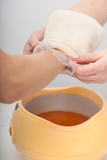 Female hand and orange paraffin wax bowl. Woman in beauty salon poster