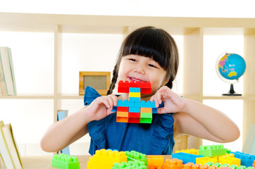 Asian kid piling up building blocks