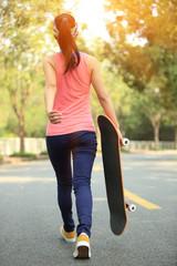 woman taking a skateboard walking on road