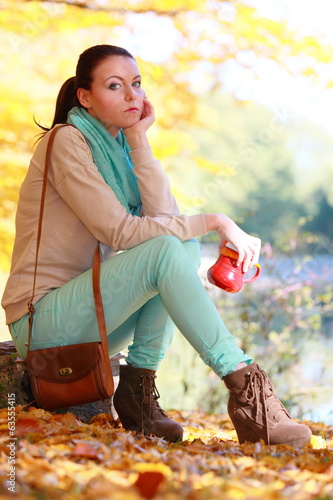 Girl relaxing in the autumn park enjoying hot drink