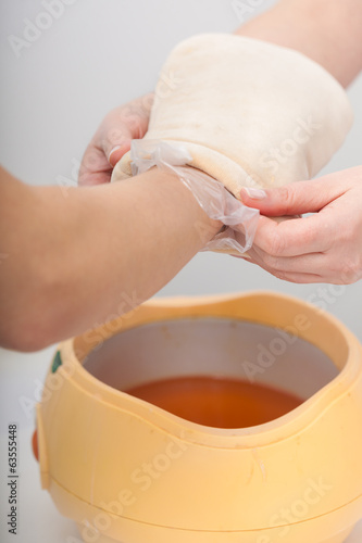 Female hand and orange paraffin wax bowl. Woman in beauty salon