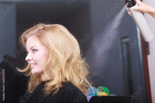 Hairstylist with hairspray and female client blond girl in salon