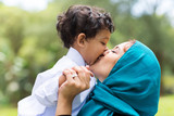 muslim mother kissing her baby boy