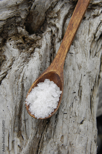 sea salt in a wooden spoon on old wood texture