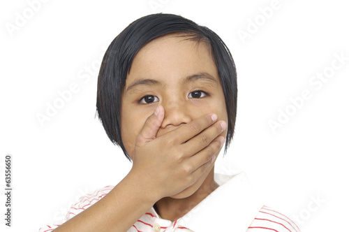 portrait of amazed small girl covering her mouth