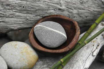 Bowl of stone with thin bamboo grove on old wood