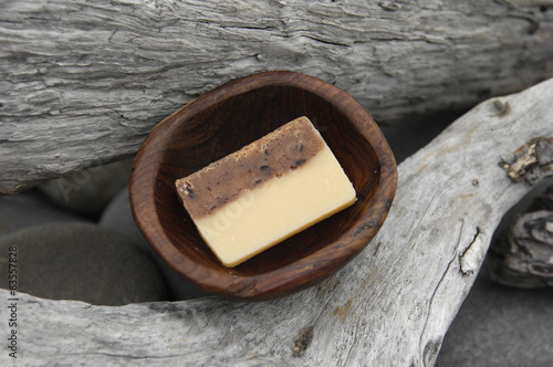 handmade natural soap in wooden bowl on Driftwood