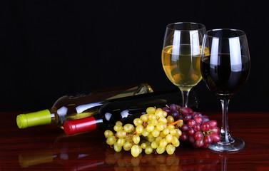 Wine Bottles and Glasses of Wine over black background.