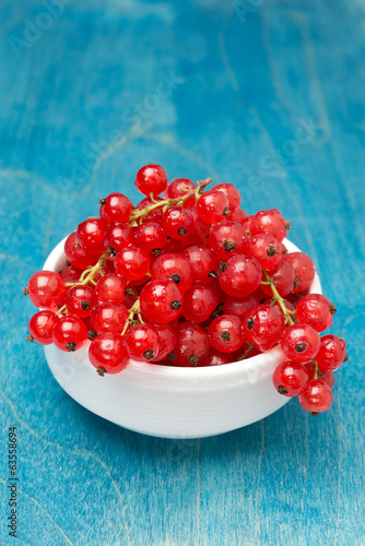 bowl of red currant on a blue wooden background, vertical