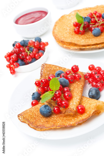 crepes with red currants, blueberries and jam for breakfast
